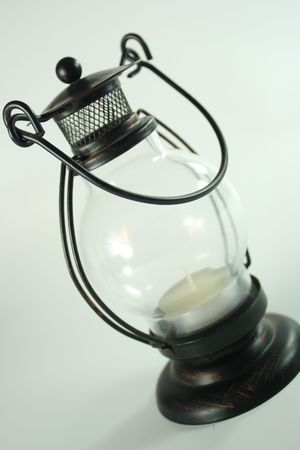 Old-fashioned lamp with candle inside isolated  photo