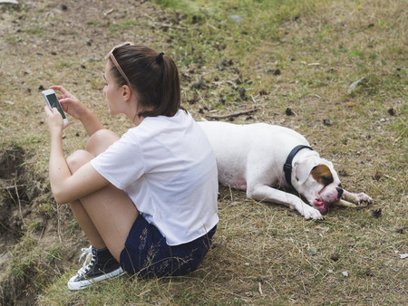 Young woman and her dog relaxing outdoors