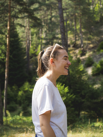 Candid portrait of a young woman laughing outdoors