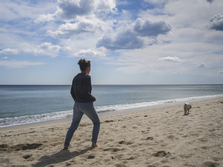 Young woman walking a dog on a sandy beach on a sunny day