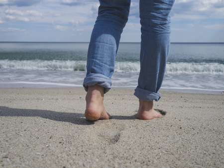 Womans bare feet walking on a beautiful sandy beach towards the water