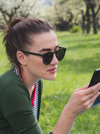 Close-up shot of a young beautiful woman texting on her smart phone while relaxing outdoors 版權商用圖片