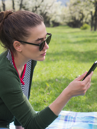 Portrait of a young beautiful woman texting on her smart phone while relaxing outdoors 版權商用圖片 - 121184413