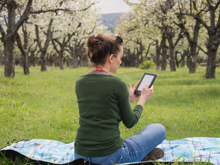 Rear view of a young woman outdoors reading on her ebook