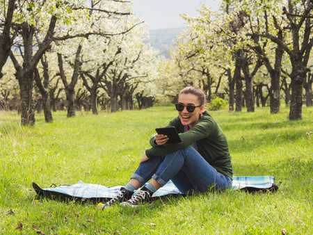 Young attractive woman reading on her ebook outdoors and laughing