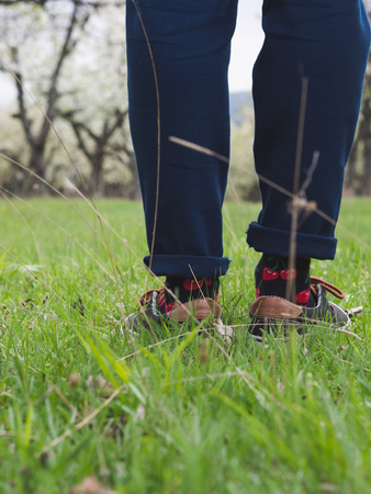 Close-up of mans legs in stylish sneakers on green grass 版權商用圖片 - 121184543