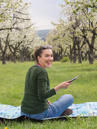 Young attractive woman holding a tablet outdoors and laughing 版權商用圖片