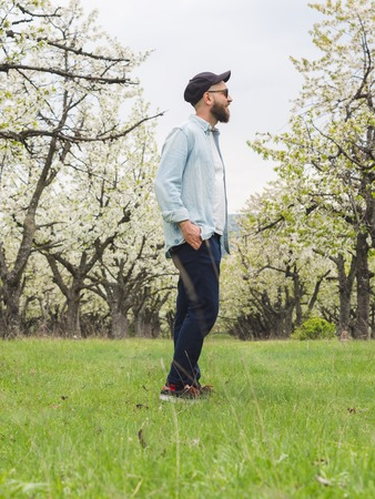 Bearded hipster man wearing casual clothes and sunglasses enjoying a walk in the nature 版權商用圖片 - 121184662