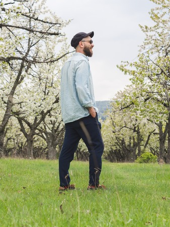 Bearded hipster man wearing casual clothes and sunglasses enjoying a walk in the nature