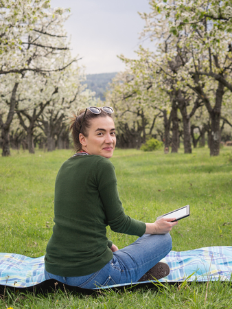Young attractive woman holding a tablet outdoors and smiling 版權商用圖片 - 121184731