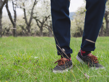 Close-up of mans legs in stylish sneakers on green grass 版權商用圖片 - 121184821