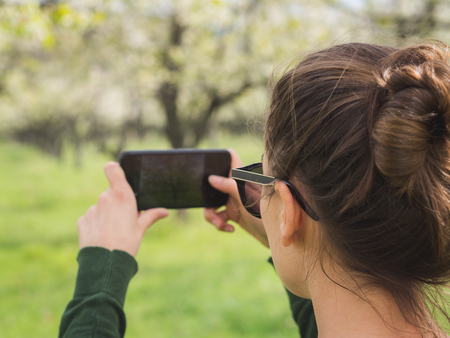 Young woman taking a picture of the view while hiking in a national park with a smart phone