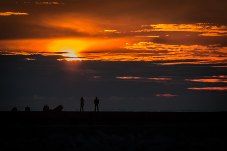 observing: Woman and man observing sunset from  breakwater Stock Photo
