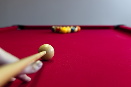 A red pool table with a player hitting the first shot