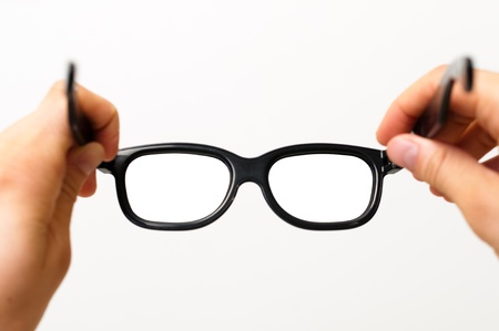 Two hands putting on thick black glasses