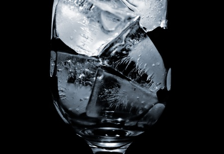 A glass filled with ice in front of a black background