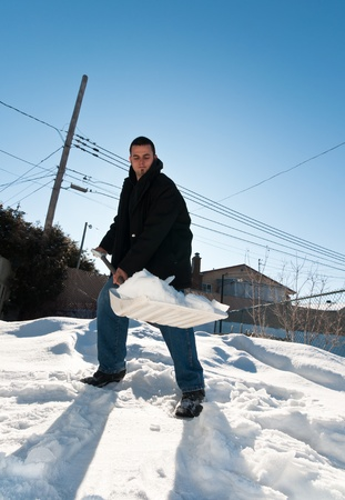 Young man shoveling some snow during winter photo