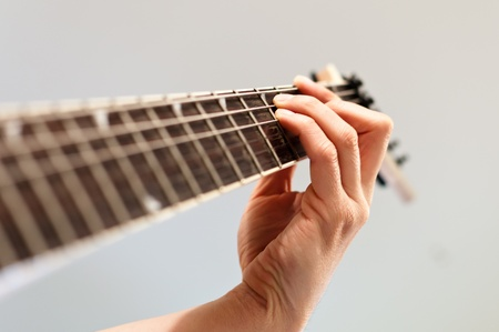 Hand playing a chord on an electric guitar photo