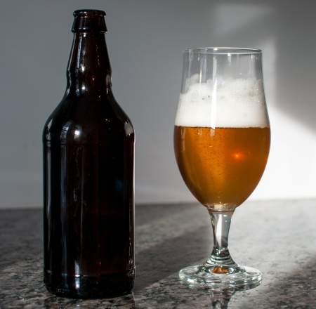Brown bottle and a beer glass on a granite counter
