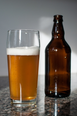 Brown bottle and a craft beer glass on a granite counter