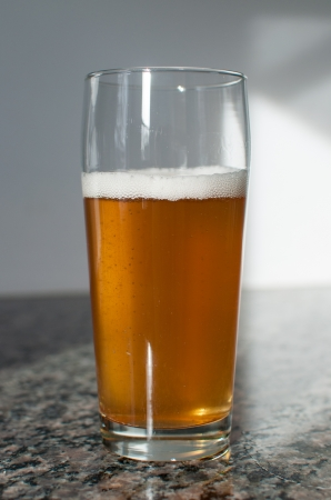 Blonde beer in a craft beer glass on a granite counter