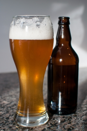 A wheat beer glass with foam and a brown bottle on a granite counter