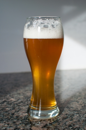 Wheat beer glass with a foamy head