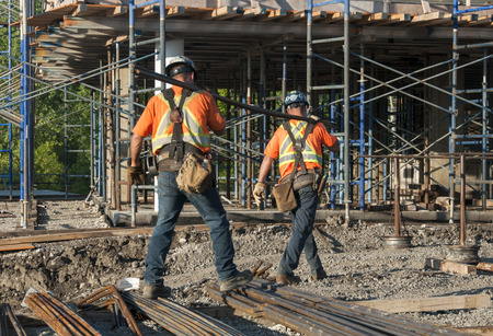 Two construction workers carrying metal rods on their shoulder