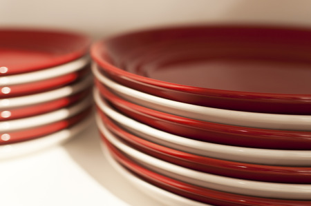 Two piles of stacked white and red plates
