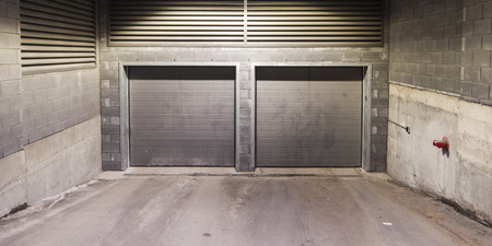 Two metal garage doors with a brick wall