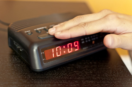snooze: Hand pressing the snooze button on a digital alarm clock