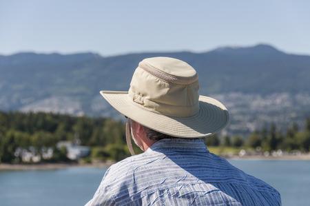 lejos: Hombre de mediana edad con un sombrero que mira lejos en el horizonte