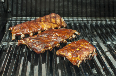 Baby back ribs cooking on the barbecue grill