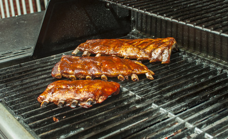 Three racks of pork ribs grilling on the barbecue