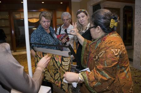 delegates: KUALA LUMPUR-JUNE 6  Meike Sahala R  expalining about batik to delegates in exhibition during Global Summit of Women 2013 in Kuala Lumpur, Malaysia on June 6, 2013   Editoriali