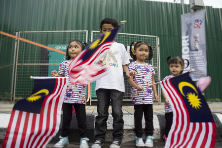 KUALA LUMPUR, MALAYSIA - AUGUST 31: Unidentified siblings wahing Malaysia national flag during celebration of Independence day 57th in Merdeka square, Kuala Lumpur, Malaysia on August 31, 2014
