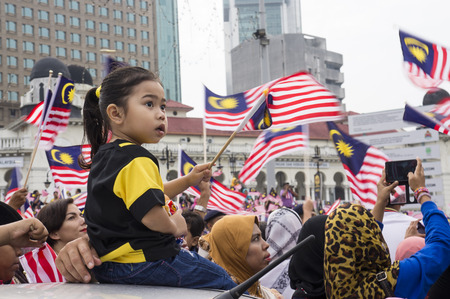 KUALA LUMPUR, MALAYSIA - AUGUST 31: Unidentified young girl waving Malaysia national flag during celebration of Independence day 57th in Merdeka square, Kuala Lumpur, Malaysia on August 31, 2014 Редакционное