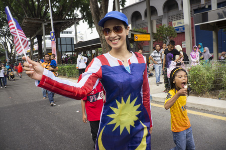 KUALA LUMPUR, MALAYSIA - AUGUST 31: Unidentified young women posing for photograph with Malaysia national flag during celebration of Independence day 57th in Merdeka square, Kuala Lumpur, Malaysia on August 31, 2014