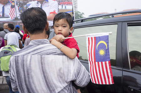 merdeka: KUALA LUMPUR, MALAYSIA - AUGUST 31: Unidentified young boy look to camera while his hand hold Malaysia national flag during celebration of 57th Independence Day in Merdeka square, Kuala Lumpur, Malaysia on August 31, 2014