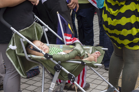 KUALA LUMPUR, MALAYSIA - AUGUST 31: Unidentified baby boy sleeping beside Malaysia national flag during celebration of Independence Day 57th in Merdeka square, Kuala Lumpur, Malaysia on August 31, 2014