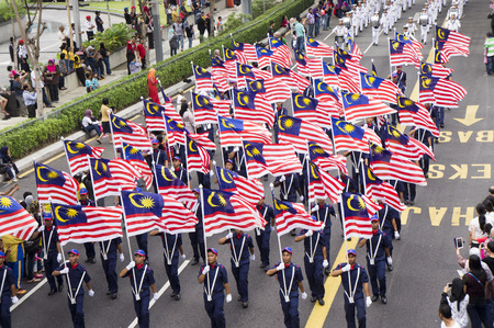 KUALA LUMPUR, MALAYSIA - AUGUST 31: Parade carrying Malaysia national flag during celebration of 57th Independence Day in Merdeka square, Kuala Lumpur, Malaysia on August 31, 2014