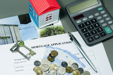 mortgage application: Close view of mortgage application form, house key, ballpoint pen, coins, money and calculator concept