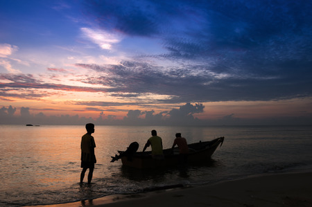 terengganu: Silhouette of traditional Malaysian fisherman preparing his boat in the morning Stock Photo