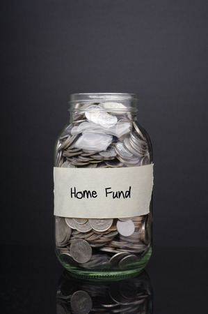 at close quarters: Home fund label on glass jar with coins