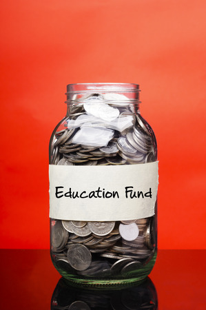 Education fund label on glass jar with coins