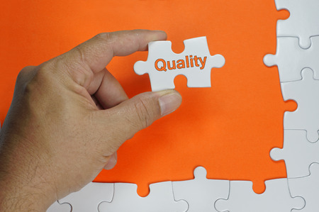 quality check: Quality word on white puzzle - Business Concept