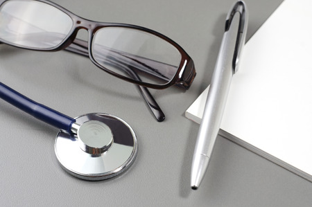 Stethoscope, eye glasses, pen and book note - Medical Concept photo