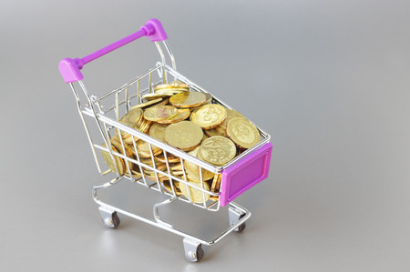meta: Isolated gold coins in the trolley - Business Concept Stock Photo