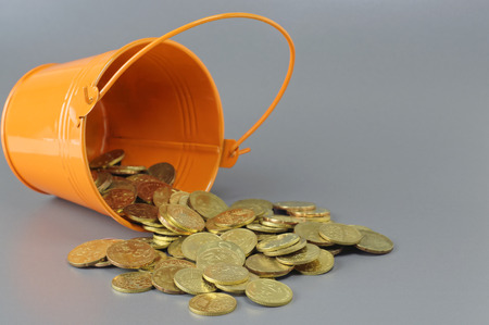 bucket of money: Gold Coins spilling out of bucket - Business Concept