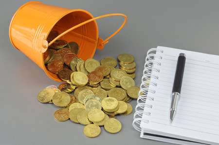 spilling: Gold Coins spilling out of bucket - Business Concept